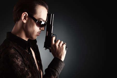 pistolas: Retrato de un joven y apuesto hombre con una pistola ..