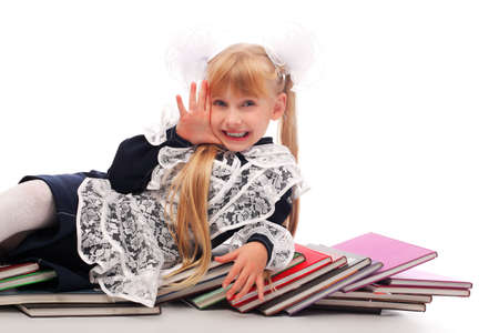Portrait of a schoolgirl on a stack of books.  photo