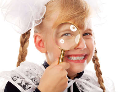 Portrait of a schoolgirl with a magnifying glass.  photo