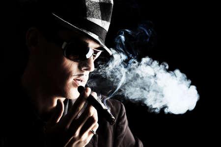 cigar smoking man: Retrato de un hombre joven y guapo en elegante traje de fumar un cigarro.