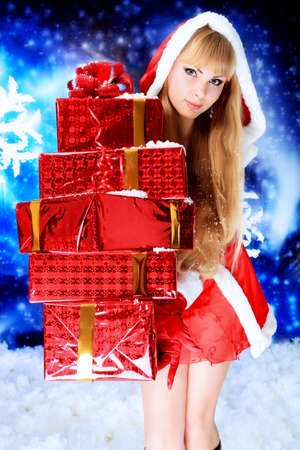 Portrait of a beautiful young woman wearing christmas clothes over sky of stars and snow. Stock Photo - 5788782