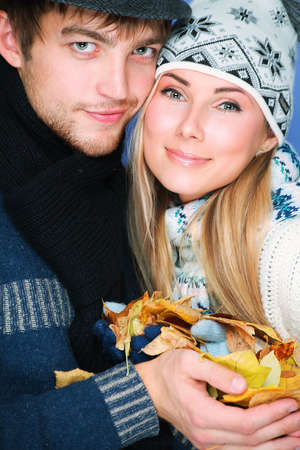 Portrait of a young couple in autumn clothes with leaves in their hands. photo