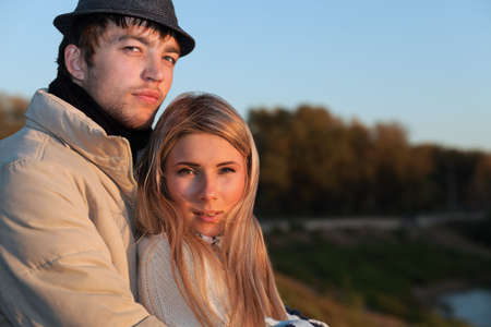Portrait of a young couple in  warm clothes watching sunset. Stock Photo - 5877135