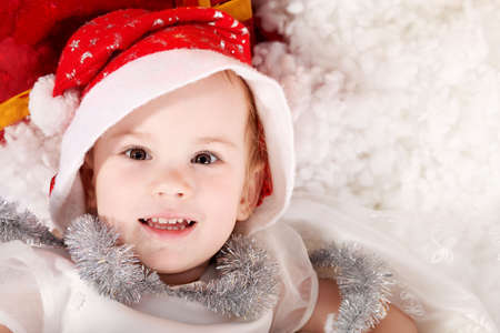 Christmas child in Santas hat lying on a snow. Stock Photo - 5911398