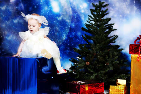 Christmas child sitting on a big present against night stellar sky. Stock Photo - 5889098