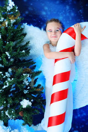 Beautiful little angelic child  with a huge candy at a christmas background. Stock Photo - 5941840