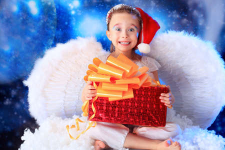 Beautiful little angelic child  with a present at a stellar sky. Stock Photo - 5941845