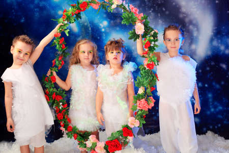Beautiful little angels holding circle of flowes at a snowy background. Stock Photo - 5941837