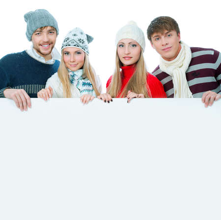 Group of young people in warm clothes holding white board. Stock Photo - 5903954