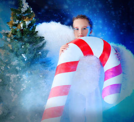 Beautiful little angelic child  with a huge candy at a christmas background. Stock Photo - 5941836