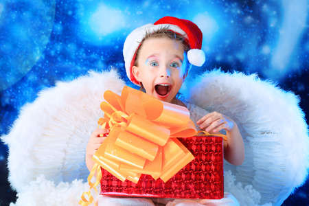Beautiful little angelic child  with a present at a stellar sky. photo