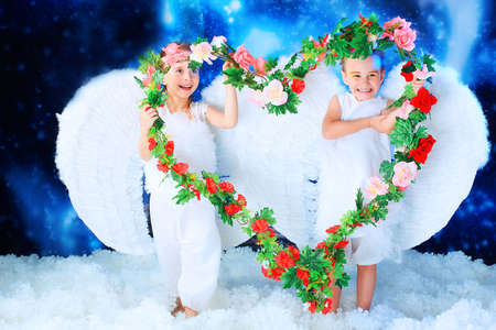 Beautiful little angels holding heart of flowes at a snowy background. Stock Photo - 5941839