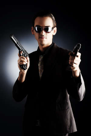 Portrait of a handsome young man holding a gun.. Stock Photo - 5927055