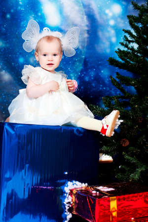 Christmas child sitting on a big present against night stellar sky. Stock Photo - 5938080