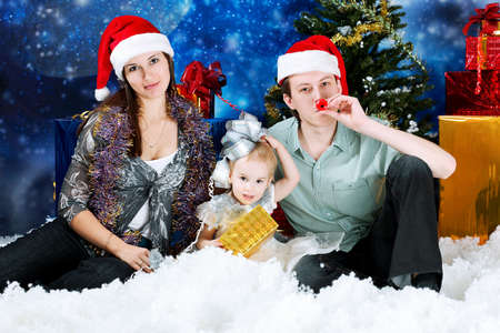Christmas theme: happy family in Santas caps sitting together on a snow. photo
