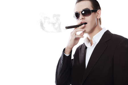 Portrait of a handsome young man in elegant suit smoking a cigar. photo