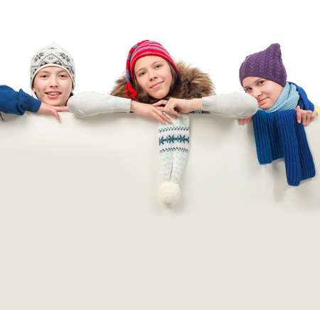 Group of teenagers in warm clothes looking out white board. Stock Photo - 6078907