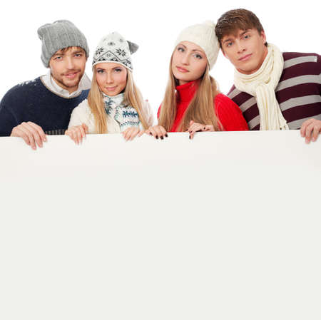 Group of young people in warm clothes holding white board. photo
