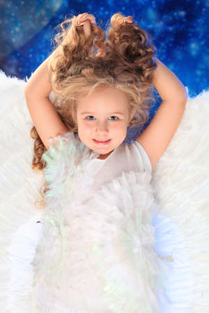 defenceless: Beautiful little angel at a snowy background.
