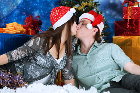 Christmas theme: happy young people in Santas caps kissing together. photo