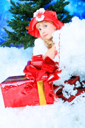Christmas kid in festive costume sitting in a snowdrift. Stock Photo - 6024835