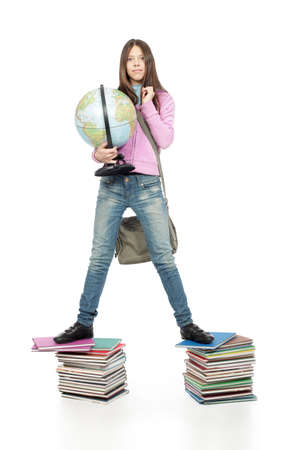 achiever: Portrait of a scoolgirl standing on a stack of books with her globe.