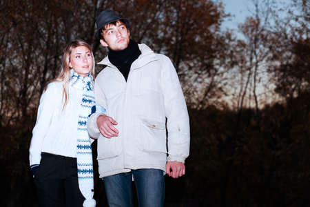 Portrait of a young couple in  warm clothes watching sunset. photo
