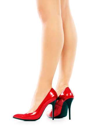 Female legs in elegant red shoes on white background photo