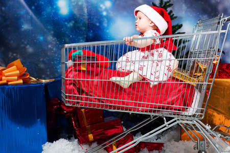 Christmas child sitting in a supermarket trolley against night stellar sky. photo