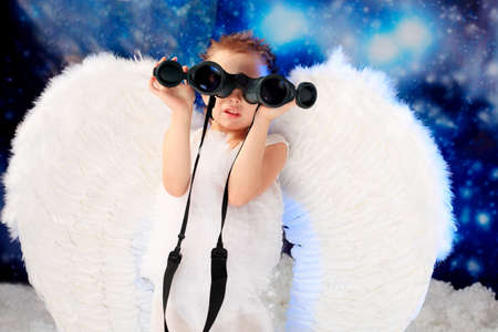 Beautiful little angel looking through his binocular,  snowy background. photo