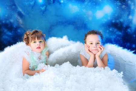Beautiful little angels at a snowy background. photo