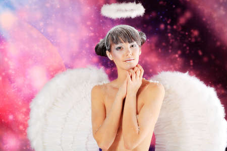 Portrait of a female christmas angel over sky of stars and snow. photo