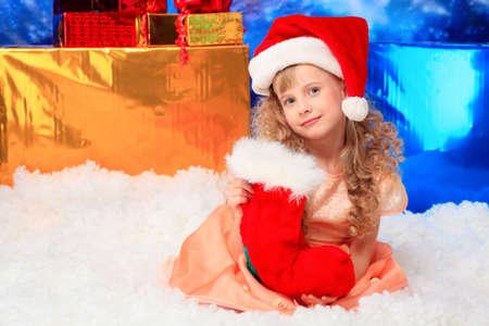 Christmas kid in Santa hat sitting in snowdrift. Stock Photo - 6098103