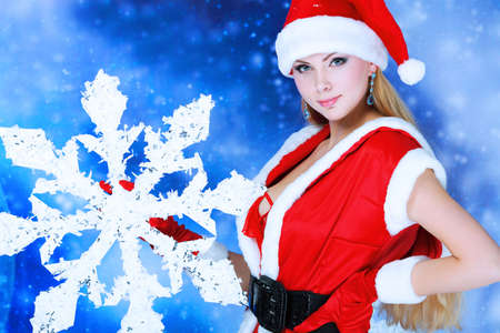 Portrait of a beautiful young woman wearing christmas clothes over sky of stars and snow. Stock Photo - 6098551