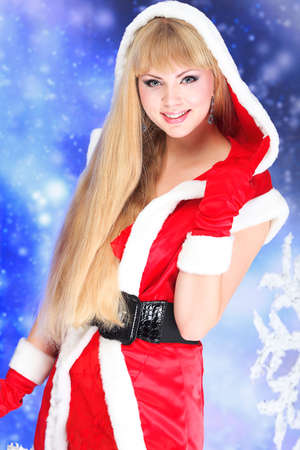 Portrait of a beautiful young woman wearing christmas clothes over sky of stars and snow. Stock Photo - 6098315