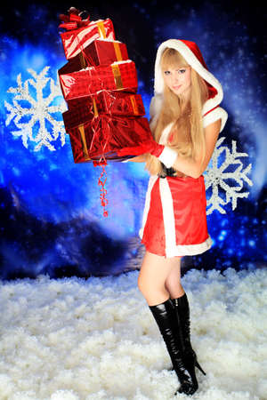 Portrait of a beautiful young woman wearing christmas clothes over sky of stars and snow. Stock Photo - 6098560