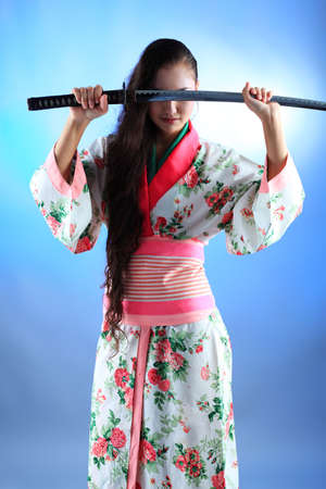 Portrait of a beautiful asian woman wearing kimono with a sword in her hands. photo
