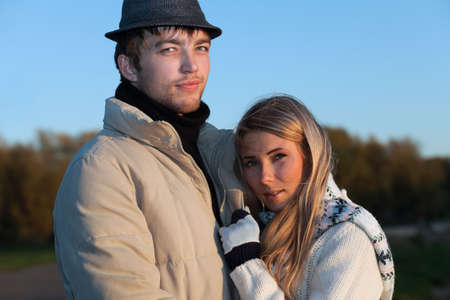 Portrait of a young couple in  warm clothes watching sunset. Stock Photo - 6098561