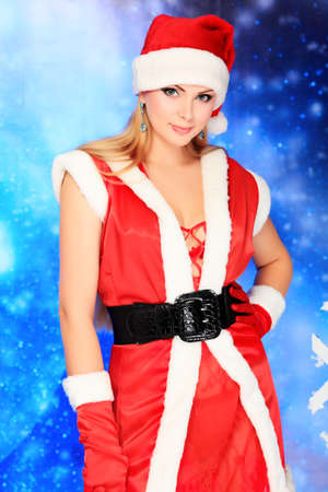 Portrait of a beautiful young woman wearing christmas clothes over sky of stars and snow. photo