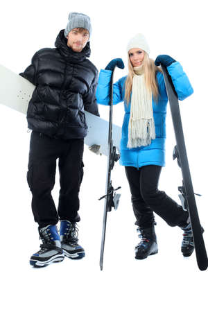 Portrait of young couple in warm clothes holding skis and snowboard. photo