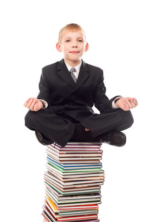 Portrait of a schoolboy sitting on a stack of books.  photo