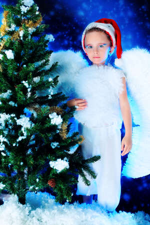 Beautiful little angelic child  at a christmas background. photo