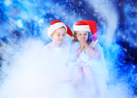 Beautiful little angelic children in a smoke at a stellar sky. photo