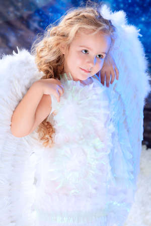 Beautiful little angel at a snowy background. photo