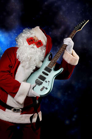 Christmas theme: Santa claus playing a guitar, snowy design. Stock Photo - 6130090