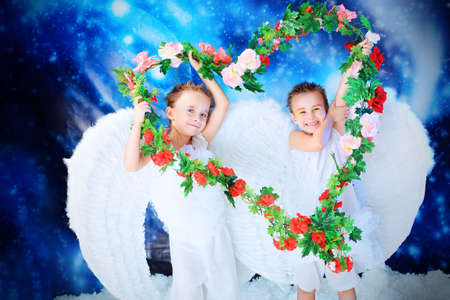 Beautiful little angels holding heart of flowes at a snowy background. photo