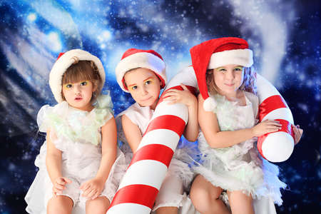 Beautiful little angelic children  with a huge candy at a christmas background. photo