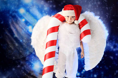 Beautiful little angelic child  with a huge candy at a christmas background. photo