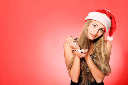 Portrait of a beautiful young woman wearing christmas clothes over red background. photo