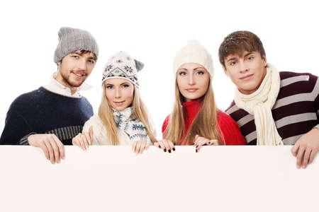 warm clothes: Gruppo di giovani in abiti caldi azienda bordo bianco.